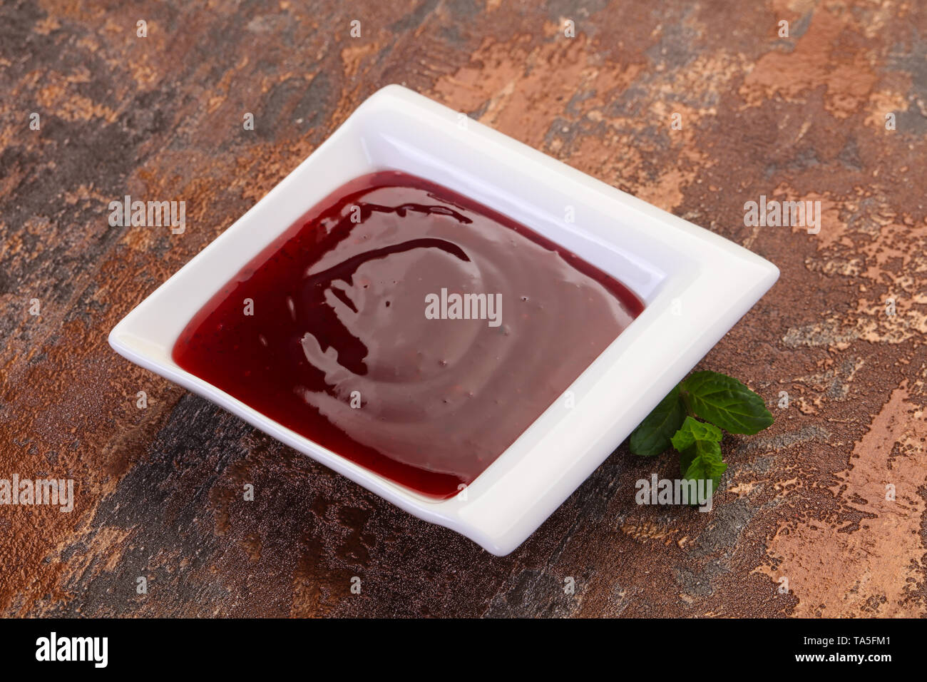 Delicous cowberry sauce with mint leaves - Stock Image