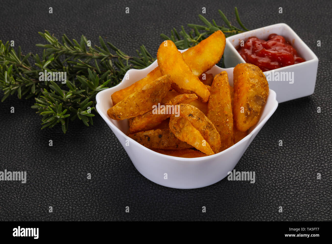 Fried potato slices with rosemary and sauce - Stock Image