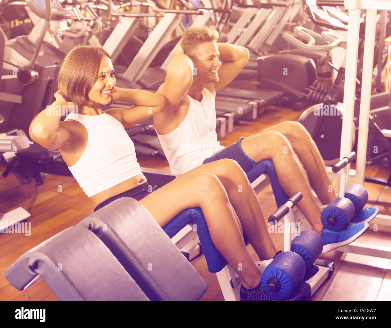 cheerful spanish man and woman making sit ups together using machine in gym - Stock Image