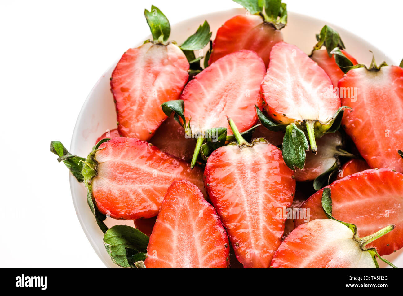 Freshly sliced strawberries. Plate with organic fresh strawberry slices for fruit salad. - Stock Image