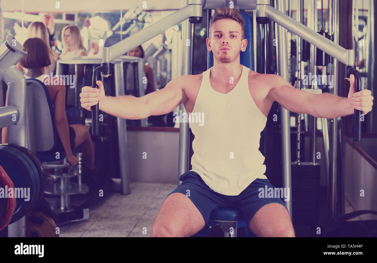 young spanish well trained man using pec deck gym machinery indoors - Stock Image