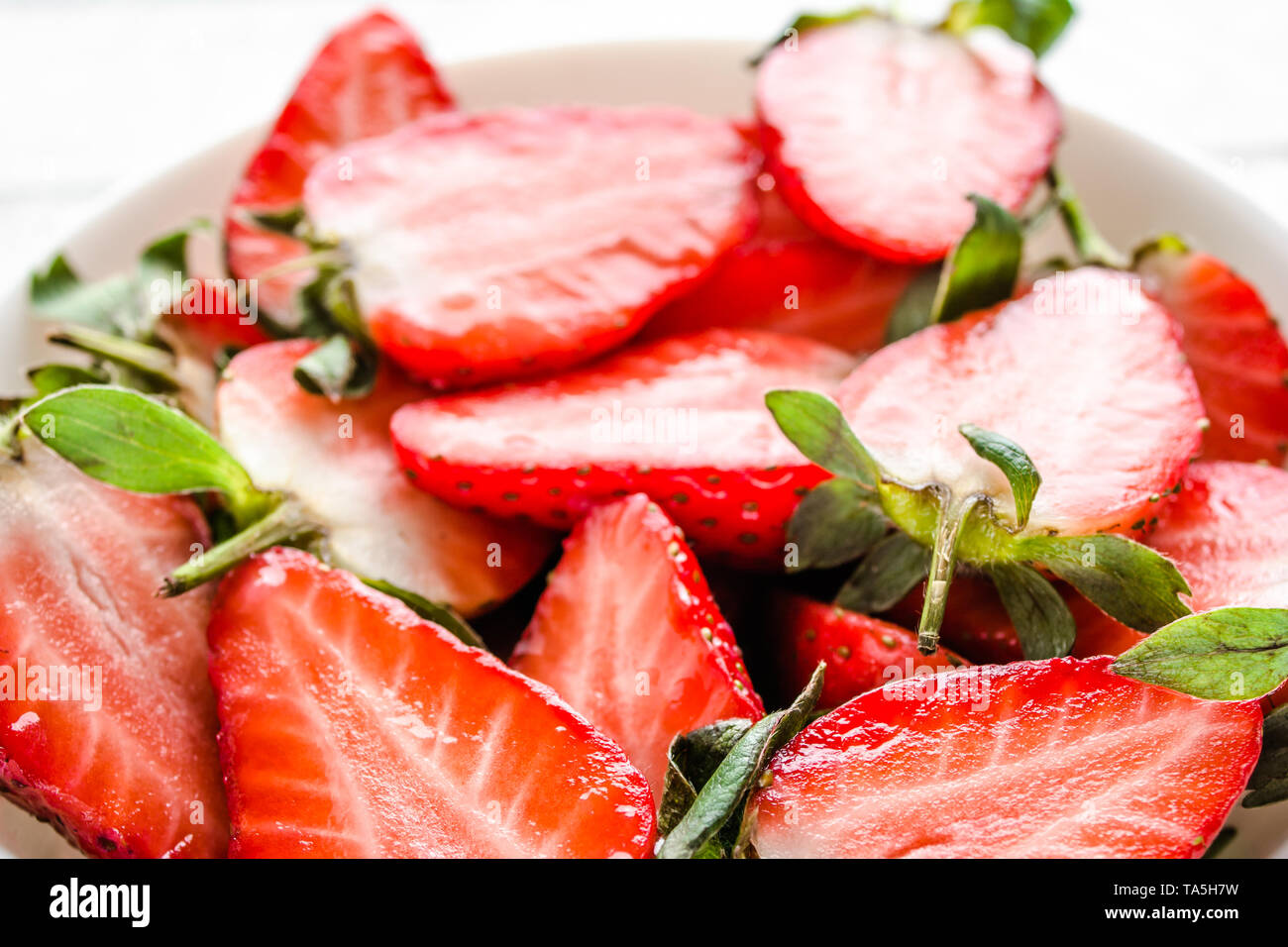 Fresh strawberries. Plate with juicy strawberry slices. - Stock Image
