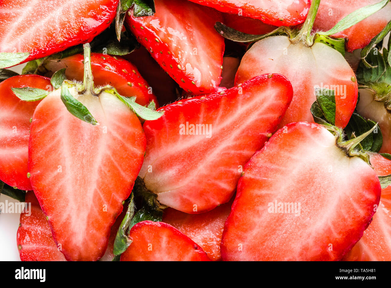 Fresh strawberries background, red texture of strawberry slices. - Stock Image