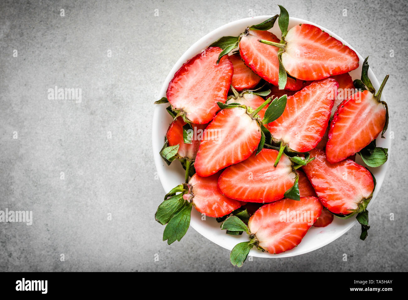 Fresh strawberry, top view. Plate with juicy slices of strawberries. - Stock Image