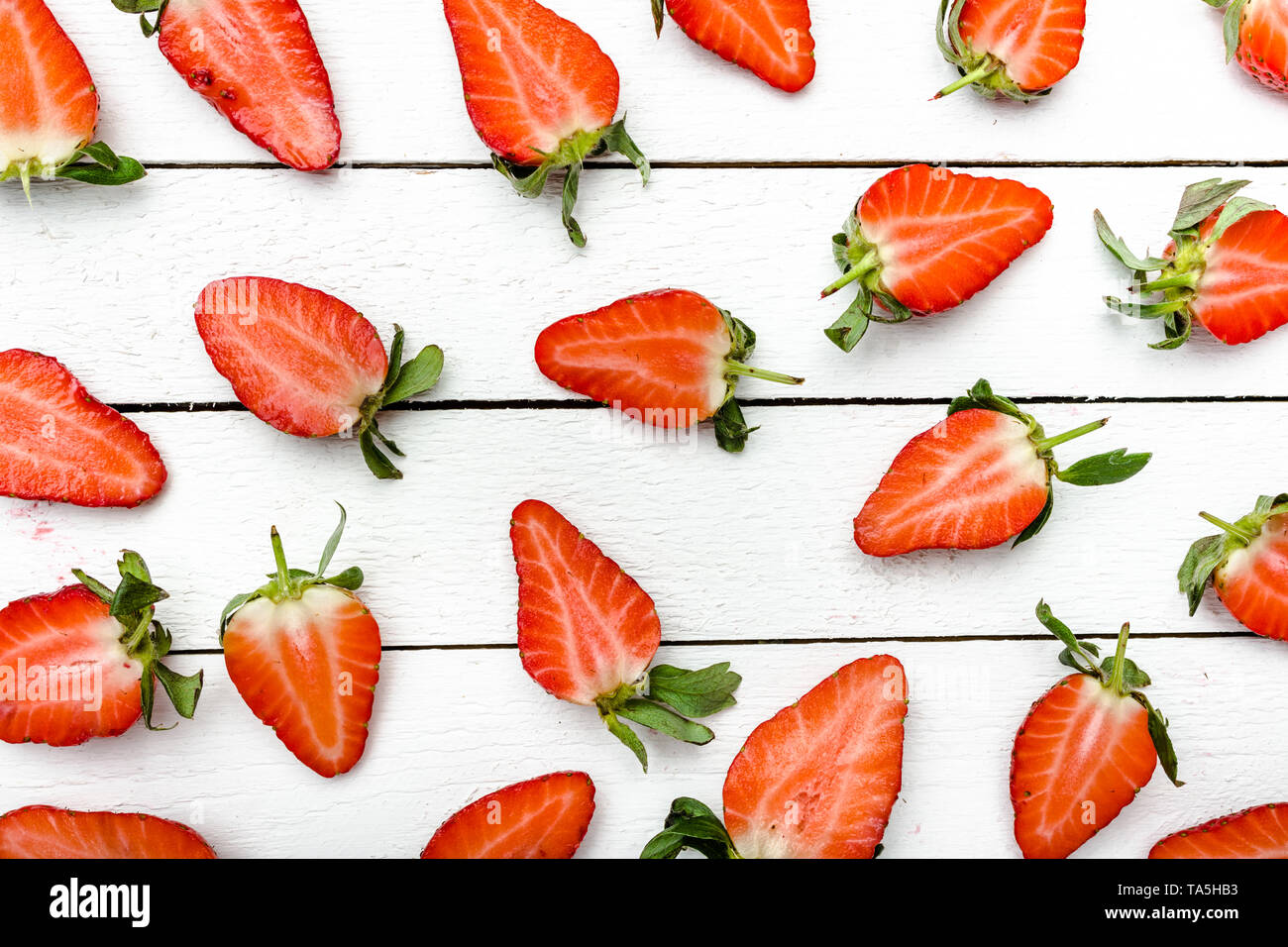 Fresh strawberries pattern. Texture of strawberry slices on white wooden background, food flat lay. - Stock Image