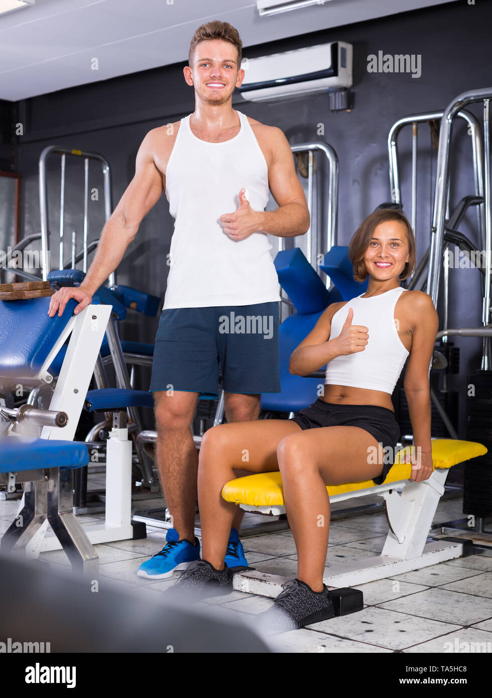 Smiling young man and woman taking pause between exercising in gym indoors - Stock Image