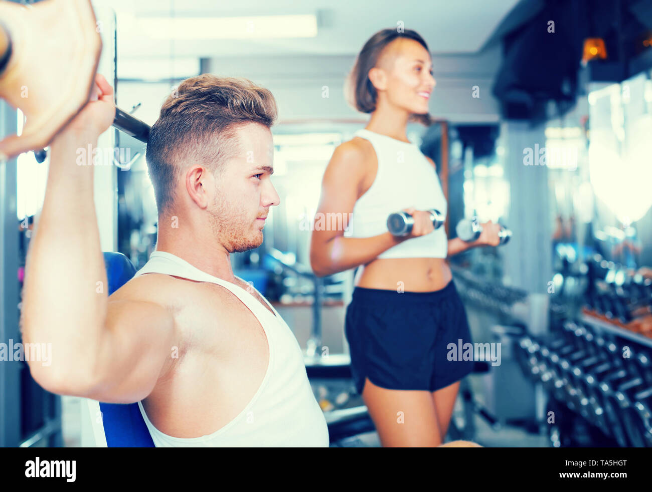 strong young man training upper body using barbell with heavy weights in gym - Stock Image