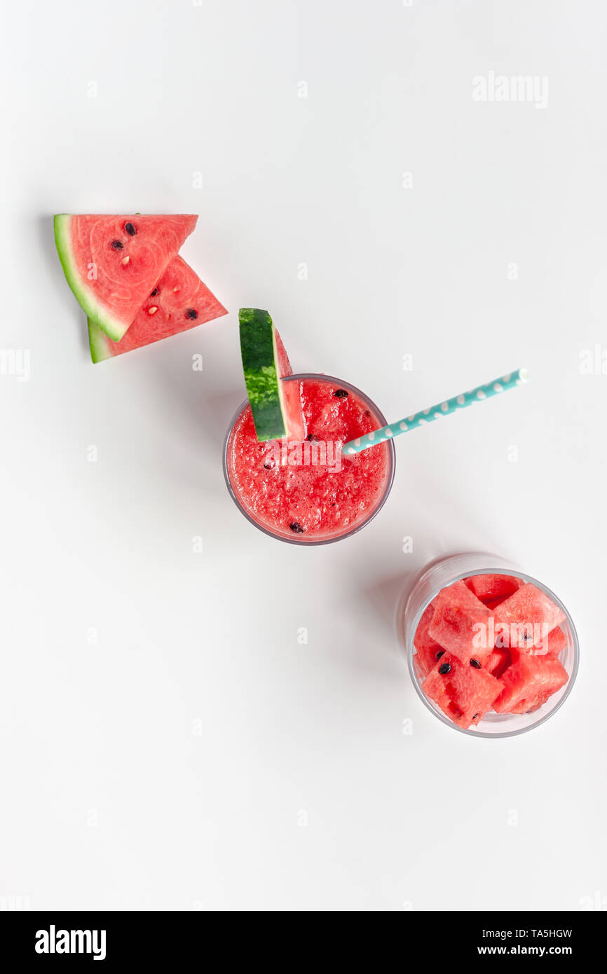 Creative scandinavian style flat lay top view of fresh watermelon slices smoothie drink in glass on white table background copy space. Minimal summer  - Stock Image