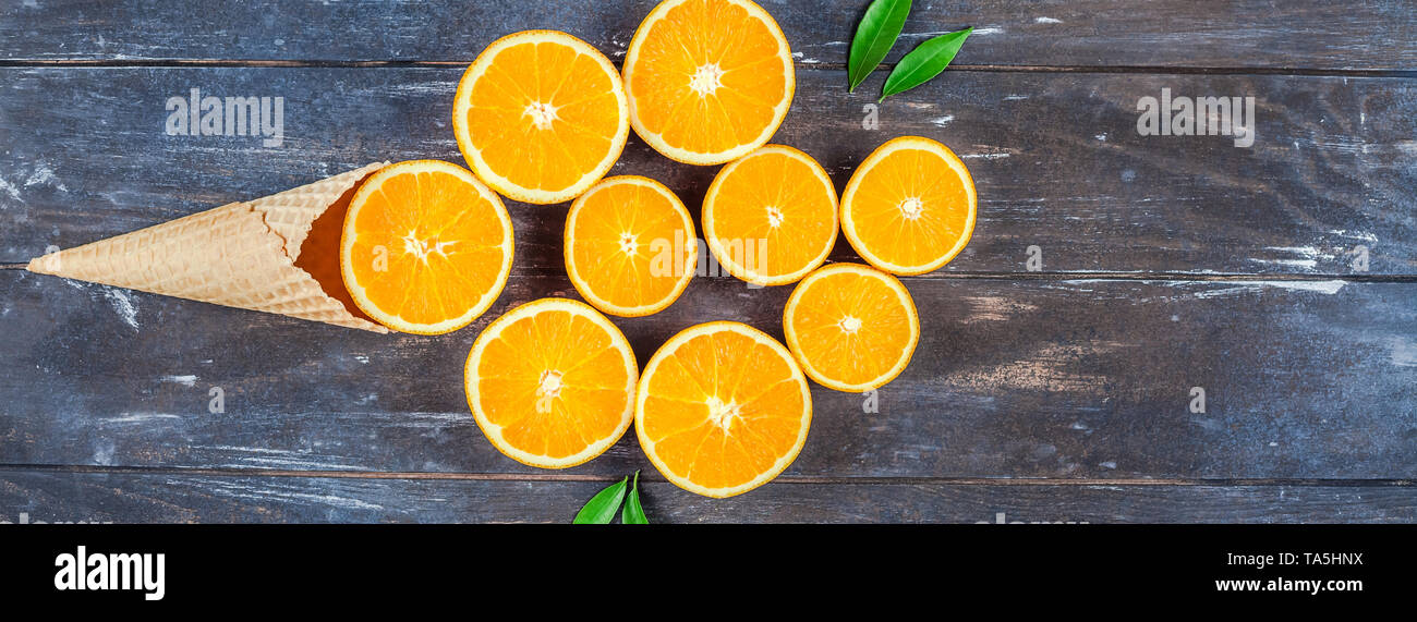 Creative dark style flat lay top view of fresh orange fruit slices in ice cream waffle cone on brown wooden table background with copy space. Minimal  - Stock Image