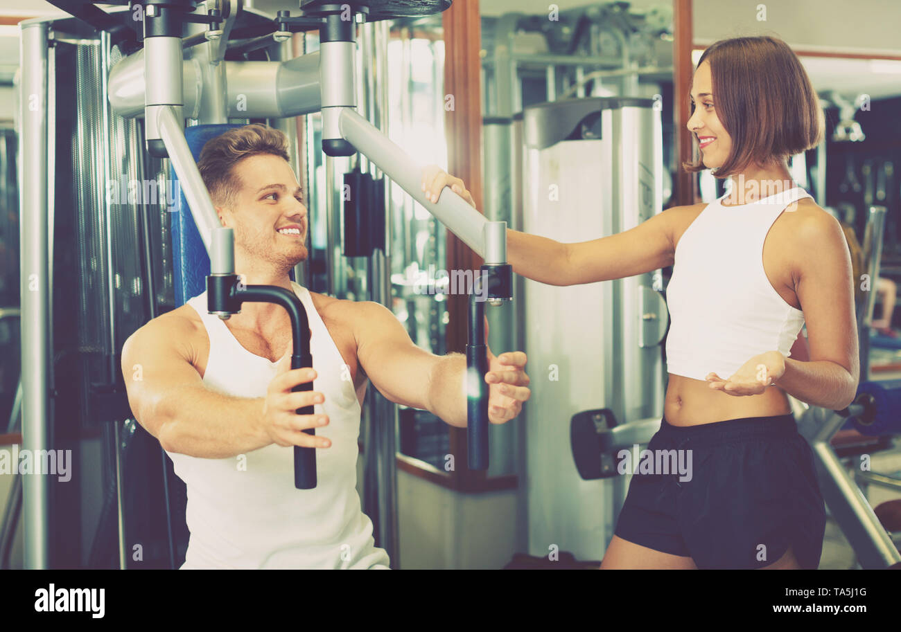 Young happy smiling female coach assisting man using fly machine in gym - Stock Image