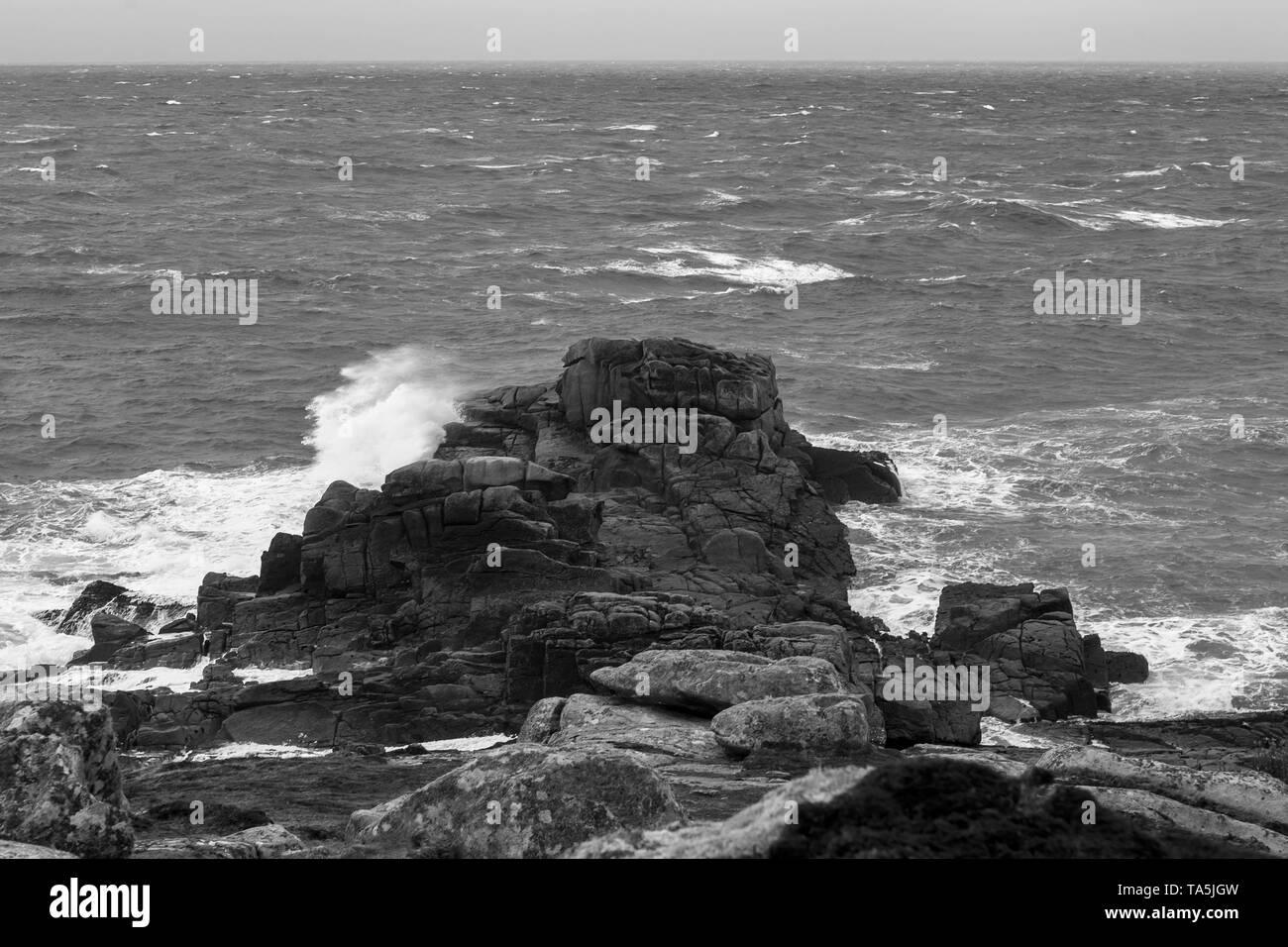 Porth Hellick Point at low tide and in a strong onshore wind, St. Mary's, Isles of Scilly, UK: black and white version - Stock Image