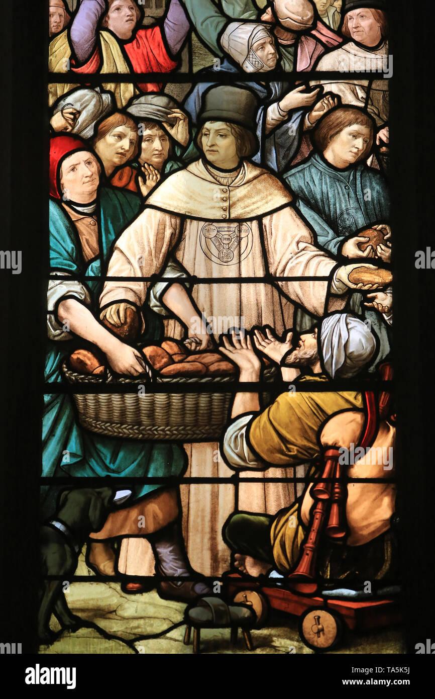 Distribution statutaire des pains aux pauvres par la confrérie. 1894. Vitrail. Eglise Saint-Nizier de Lyon.Trinity Brothers Helping the Poors. - Stock Image