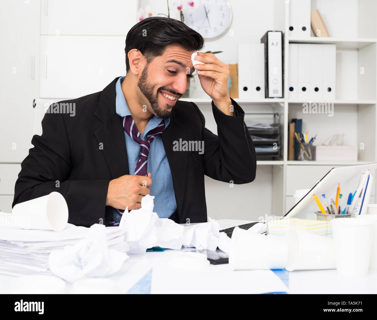 Spanish male worker is having complicated issue with project in office. - Stock Image