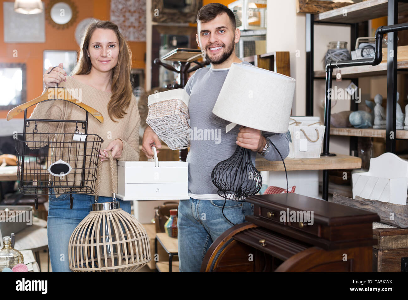 Happy couple demonstrating their buies in shop of secondhand furniture - Stock Image