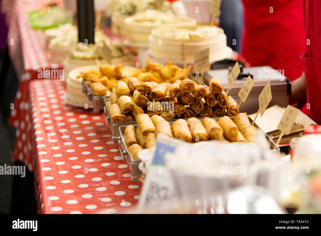 A pile of spring roll food snack on display at a food market. - Stock Image