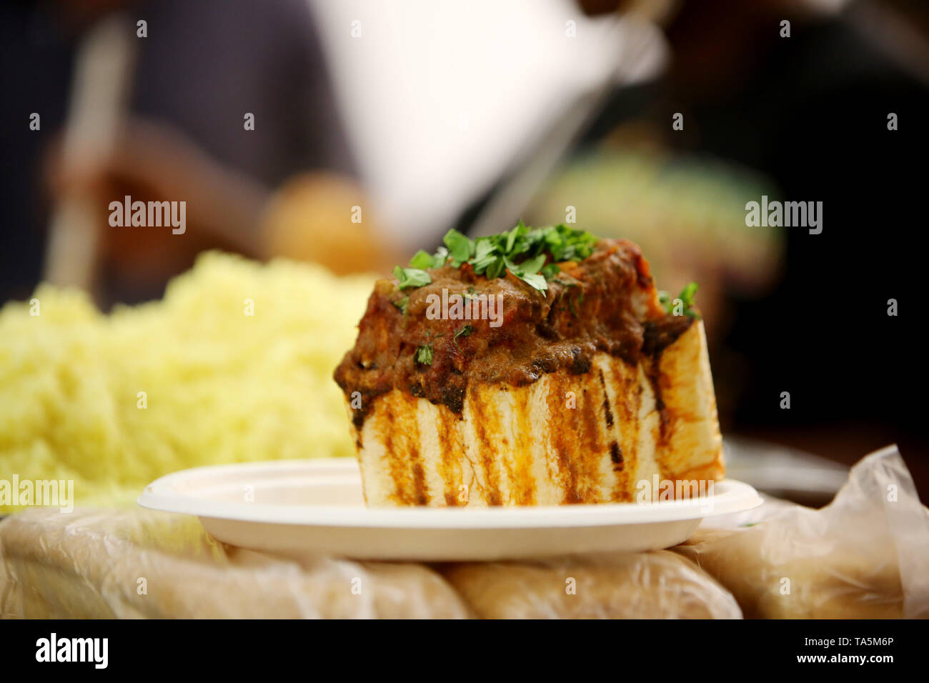 An indian inspired curry and bread fast food meal known as a bunny chow in South Africa - Stock Image