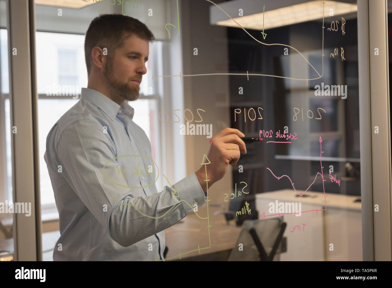 Businessman writing on glass wall - Stock Image