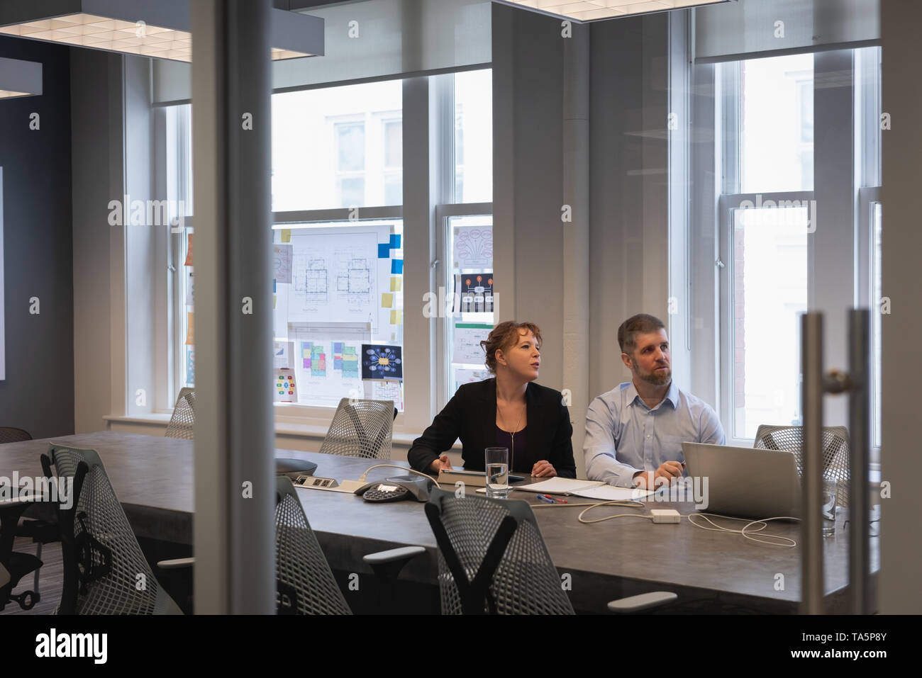 Two business people listening in a conference room Stock Photo
