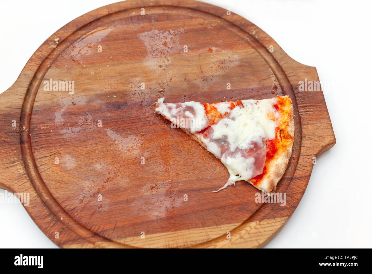 Last one slice of delicious Italian pizza with ham and cheese on wooden board on white table. Pizza time. Top view. Close-up - Stock Image