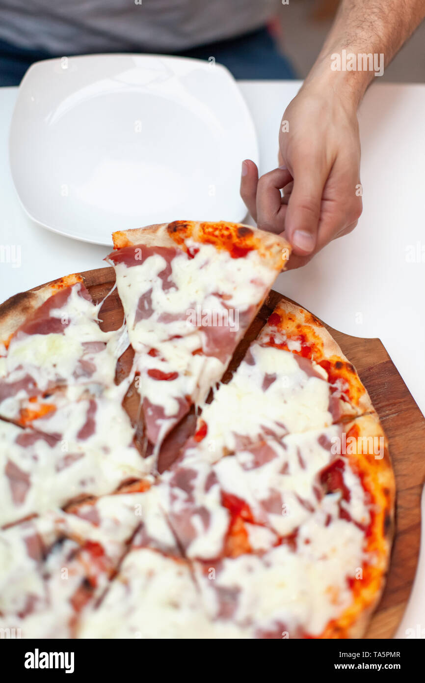 Man took first slice of delicious Italian pizza. In frame hand taking slice of hot pizza with ham on wooden board, white serving plate on white table. - Stock Image