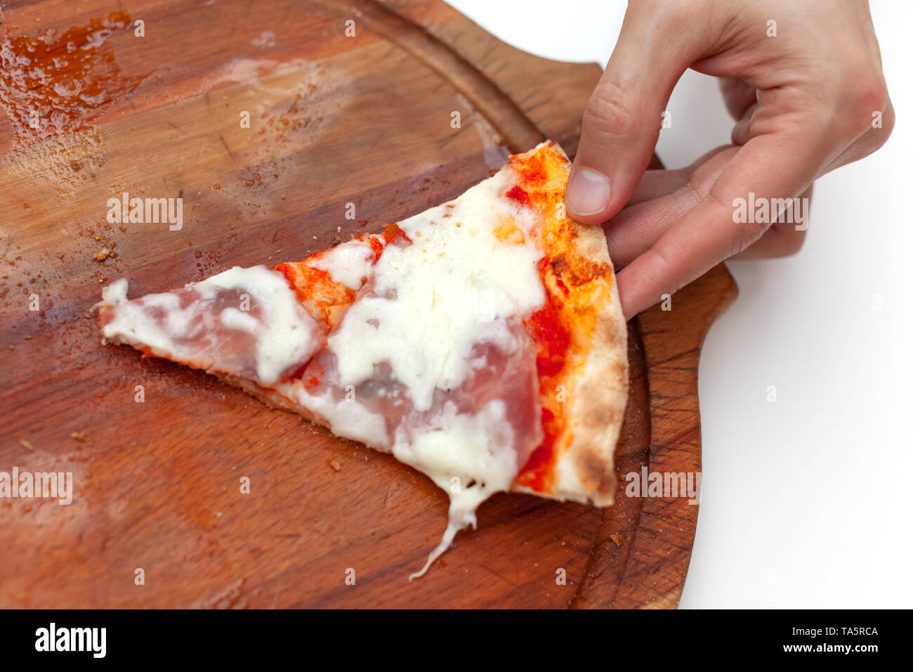 Man took last one slice of delicious Italian pizza. In frame hand taking slice of hot pizza with ham on wooden board on white table. Pizza time. Side  - Stock Image