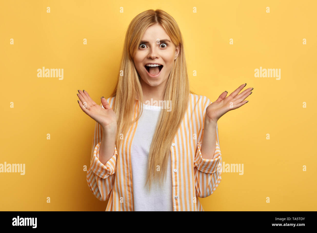 blonde awesome excited astonished woman with opened mouth screaming, raising hands, , over blue background. studio shot.big sale, happiness, luck, suc Stock Photo