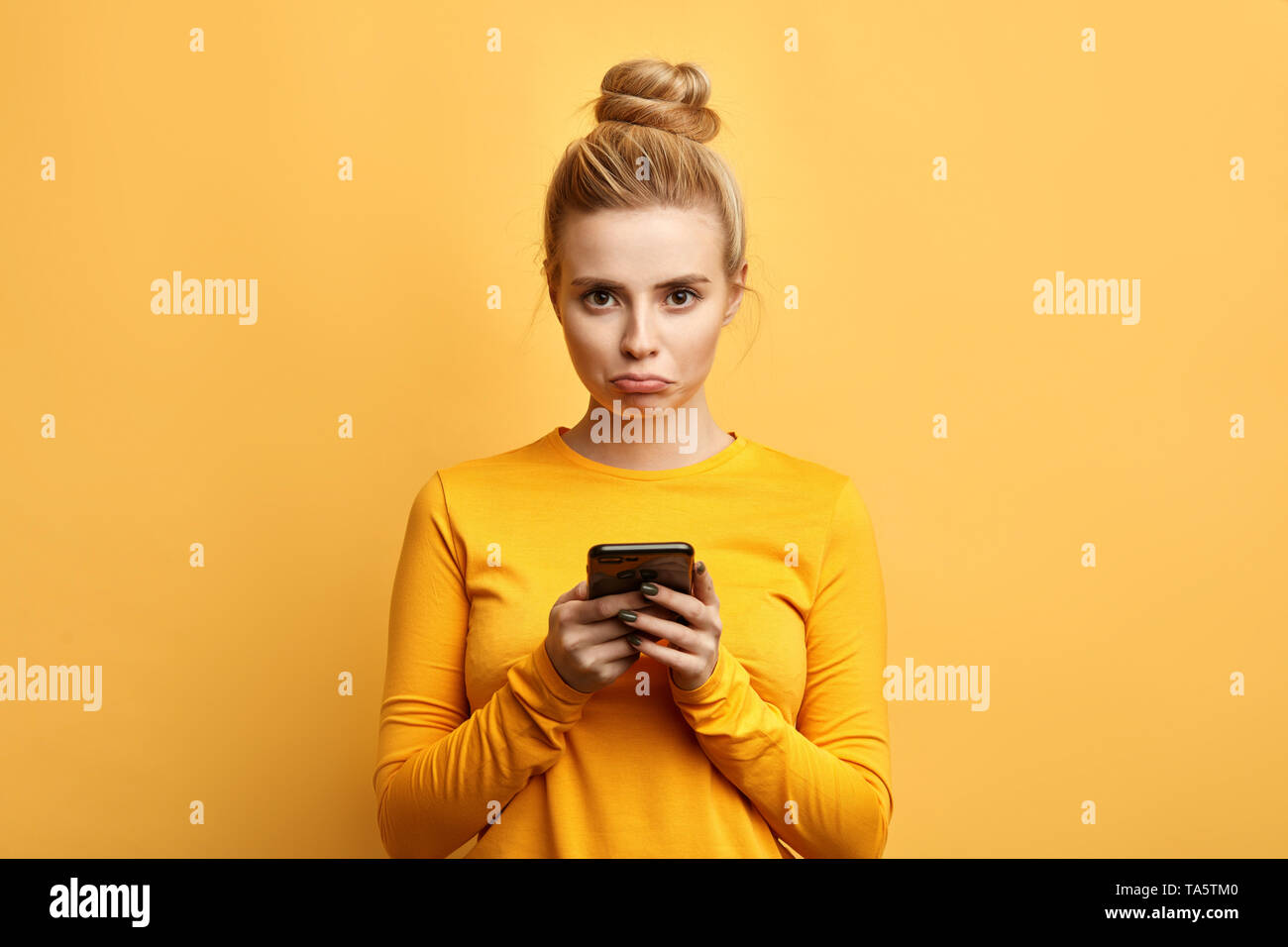 angry sad woman with hairbun annoyed by something while using phone, girl has received bad sms, text message isolated yellow background. emotion, reac - Stock Image