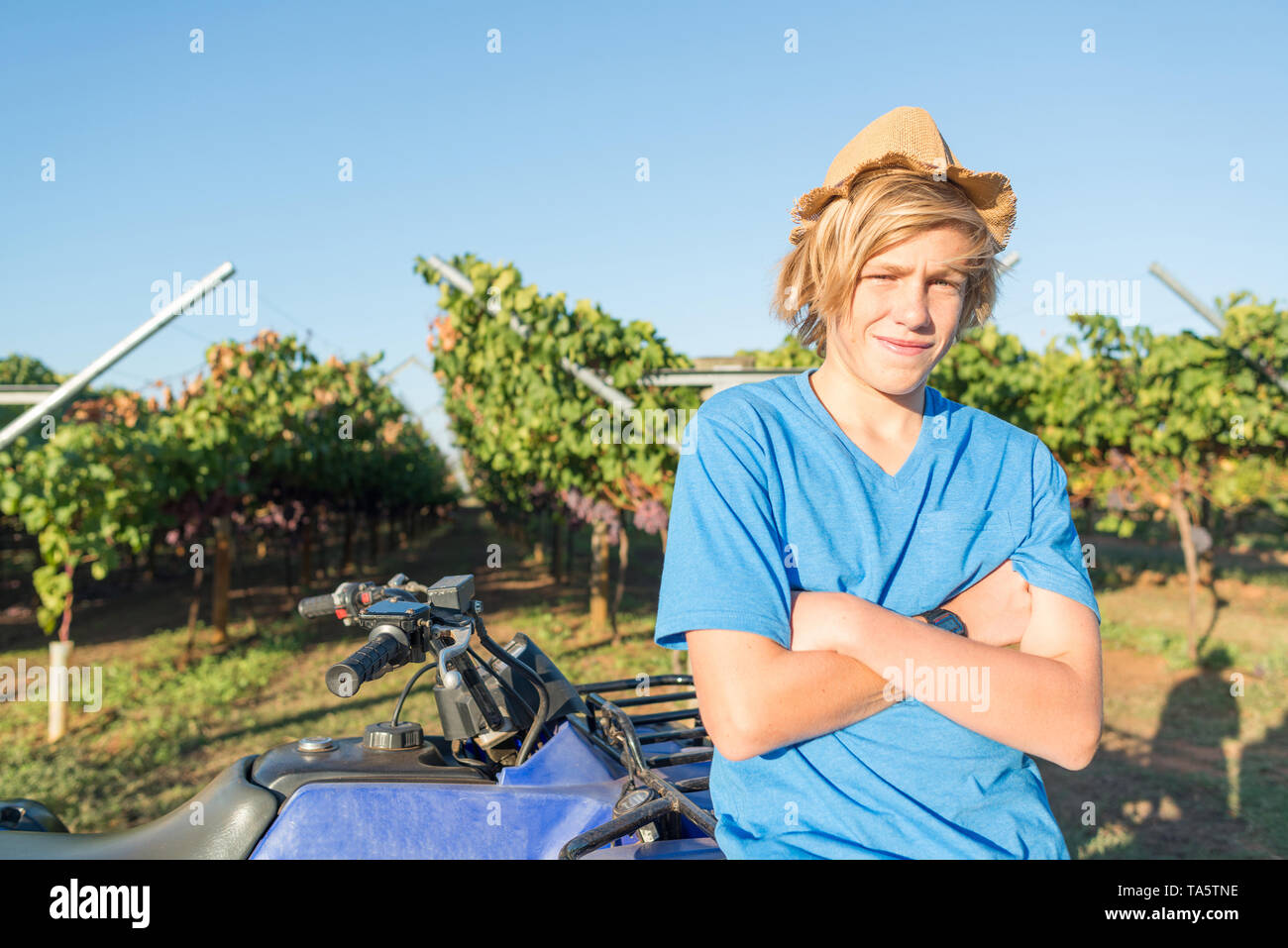Young teenager with arms folded standing - Stock Image