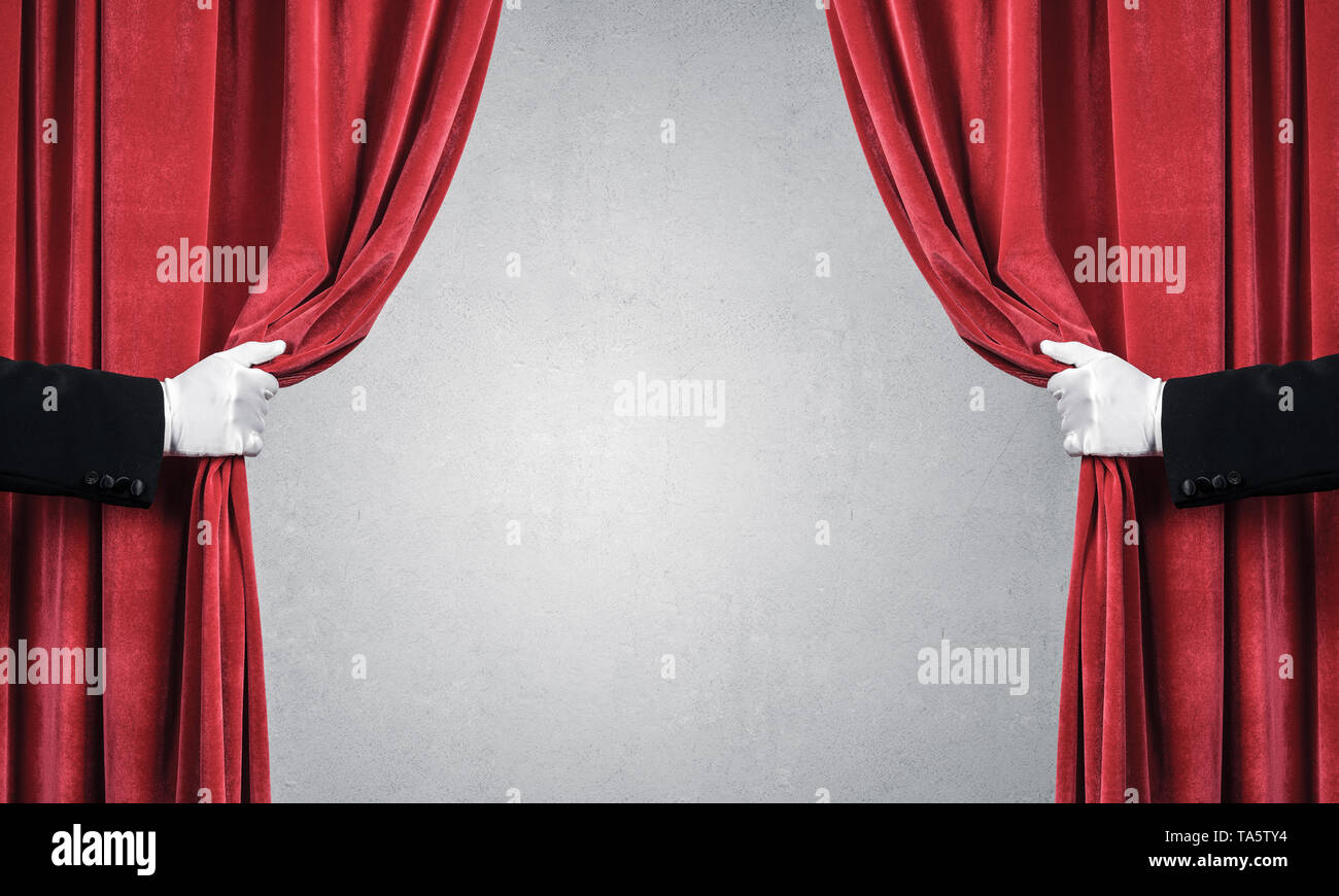 Concrete wall behind drapery curtain and hand opening it - Stock Image