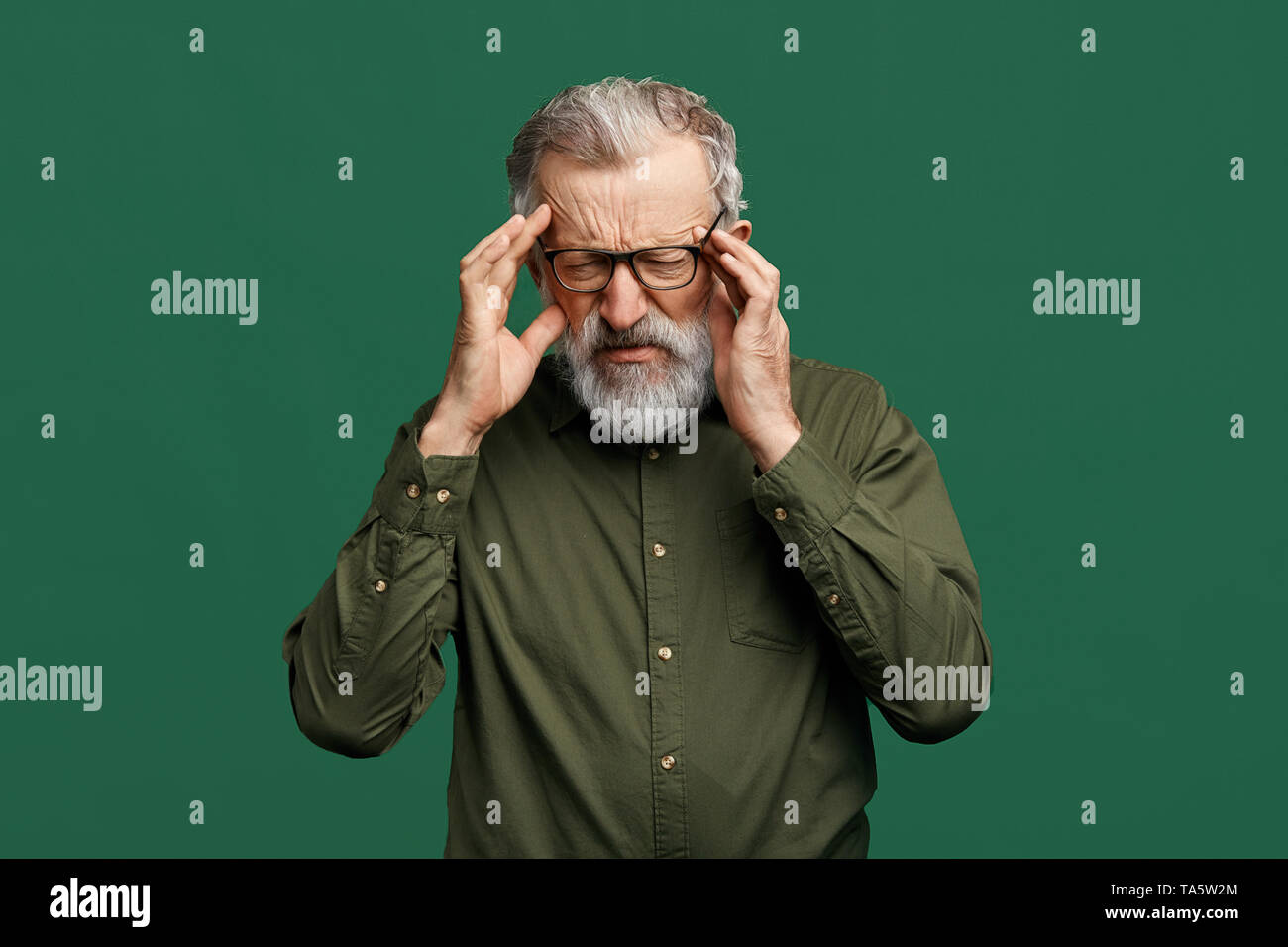 mature handsome stylish man having very strong pain and holding head isolated on green background, senoir man has bad memory, amnesia concept. weaknes - Stock Image