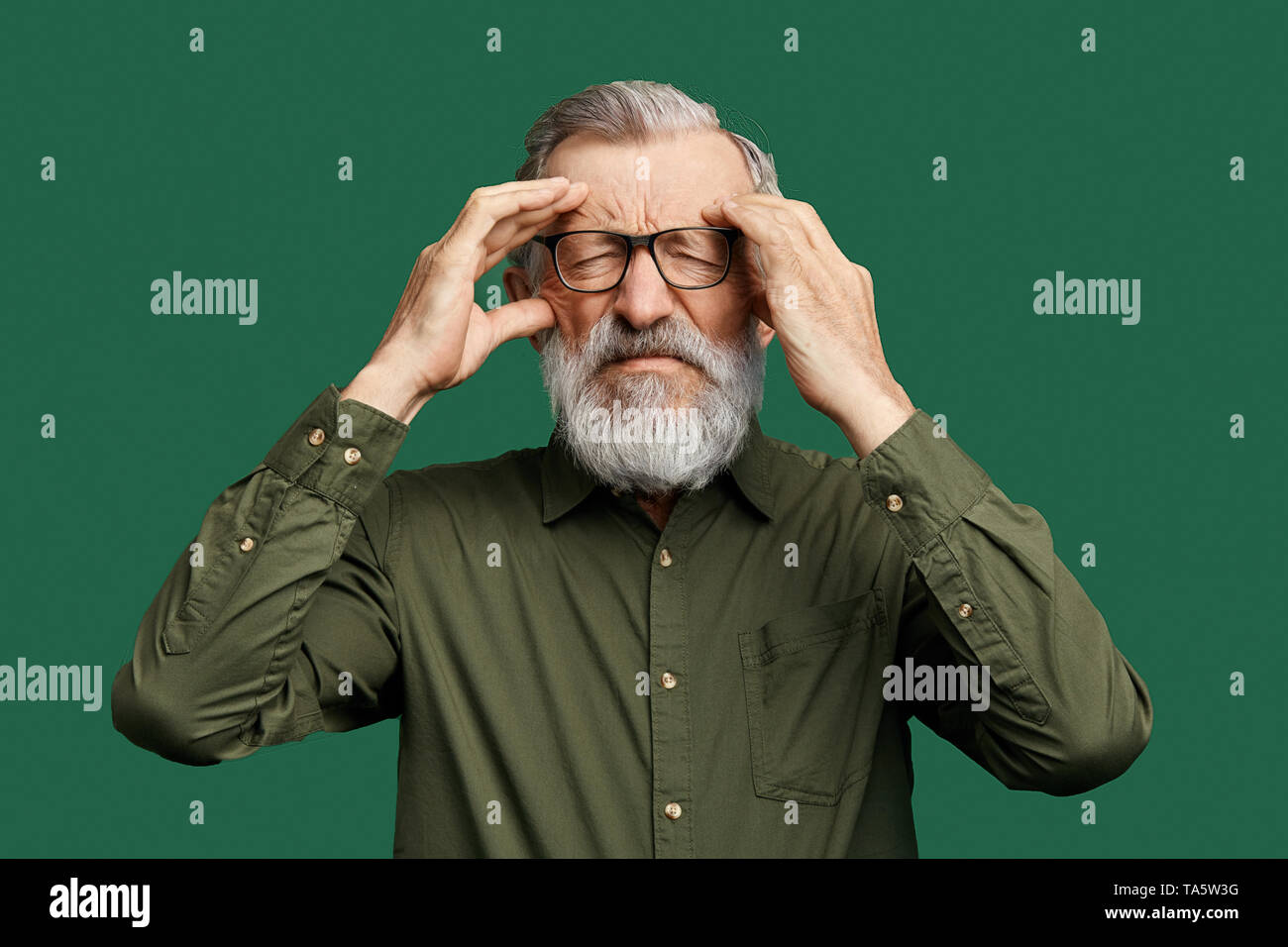 unhappy man with closed eyes trying to remember some information, facts, holding his temples, man with gray beard has lost his memory. isolated green  - Stock Image