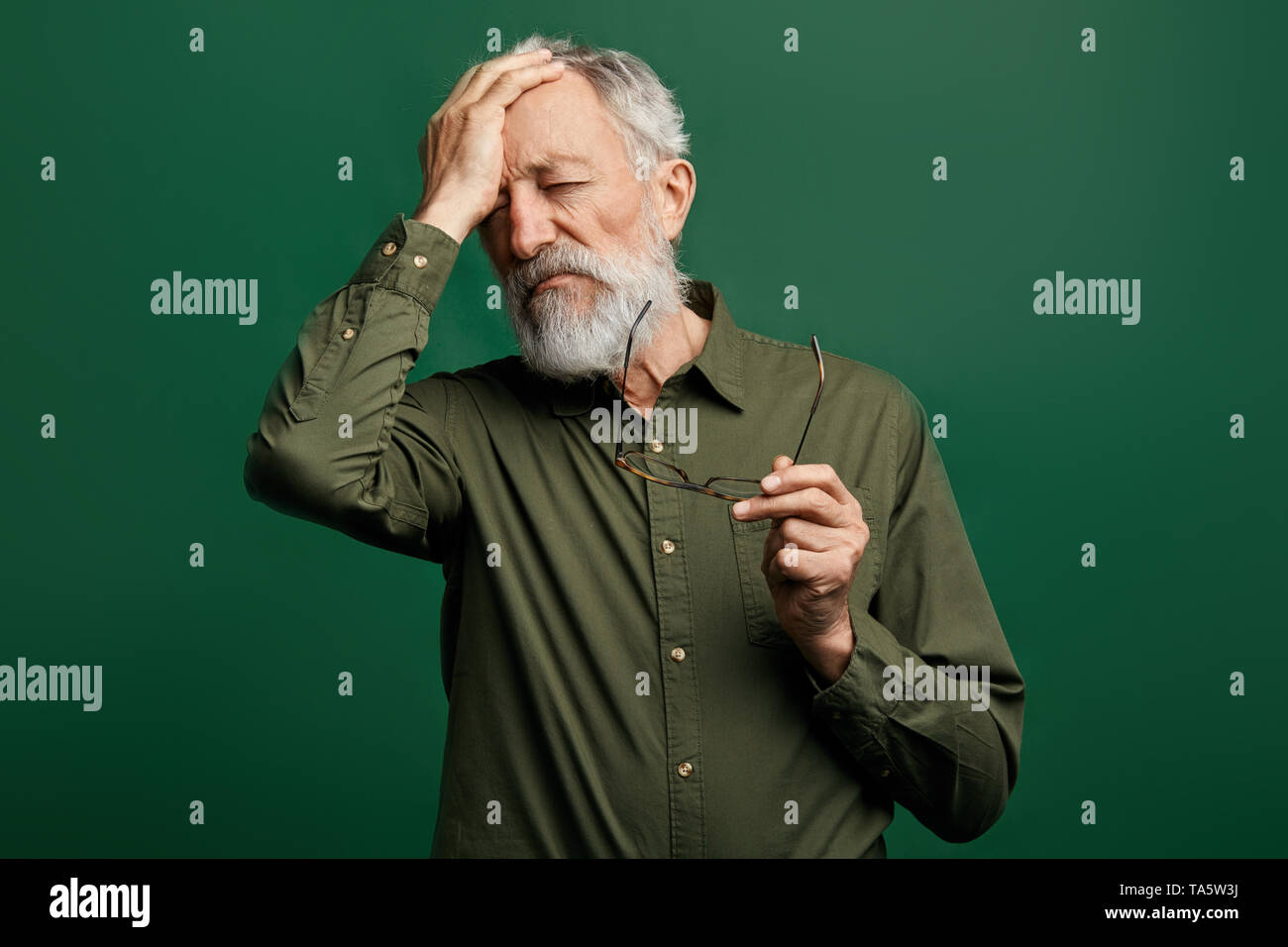 sad depressed man has a headache, taking off his glasses and touching his forehead. man has high blood pressure. old man has many problems - Stock Image