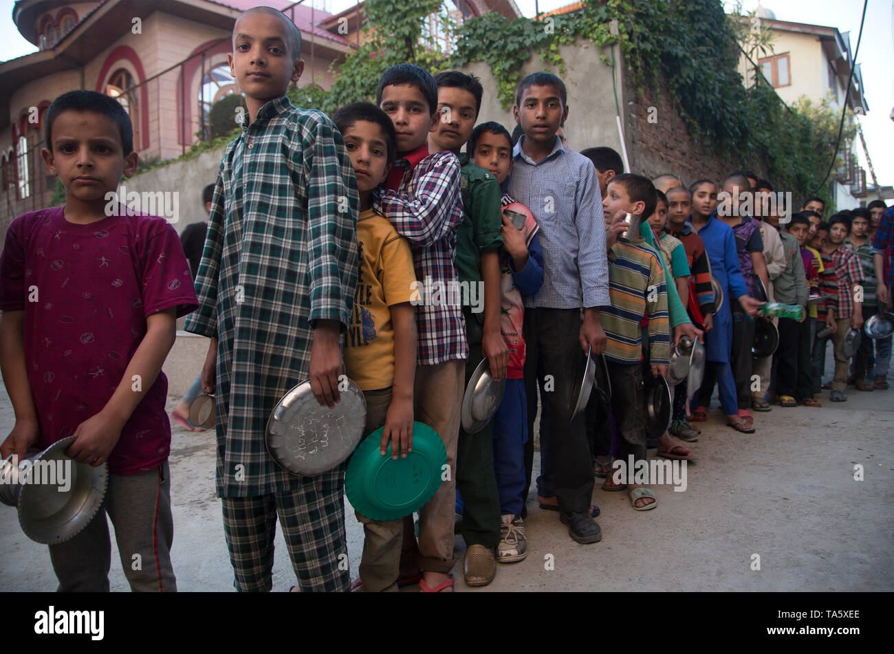 Srinagar, Indian-controlled Kashmir. 21st May, 2019. Kashmiri Muslim orphans line up to get food for Iftar, or fast-breaking meal, at an orphanage when Muslims break their fast during the holy month of Ramadan in Srinagar, the summer capital of Indian-controlled Kashmir, May 21, 2019. Credit: Javed Dar/Xinhua/Alamy Live News - Stock Image