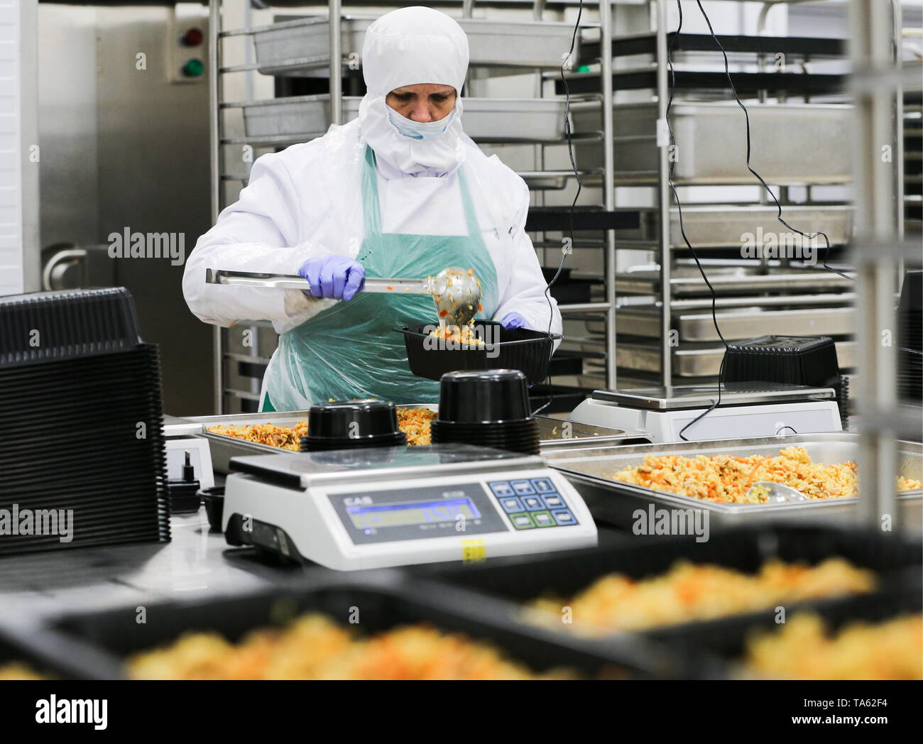 Russia. 22nd May, 2019. MOSCOW REGION, RUSSIA - MAY 22, 2019: An employee packages pilau at the Smart Kitchen launched by the Perekrestok supermarket chain; measuring 26,000sqm in area, the kitchen produces more than 200 various articles of food under the brand name Chef Perekrestok to supply to the Perekrestok supermarkets, Gavriil Grigorov/TASS Credit: ITAR-TASS News Agency/Alamy Live News - Stock Image