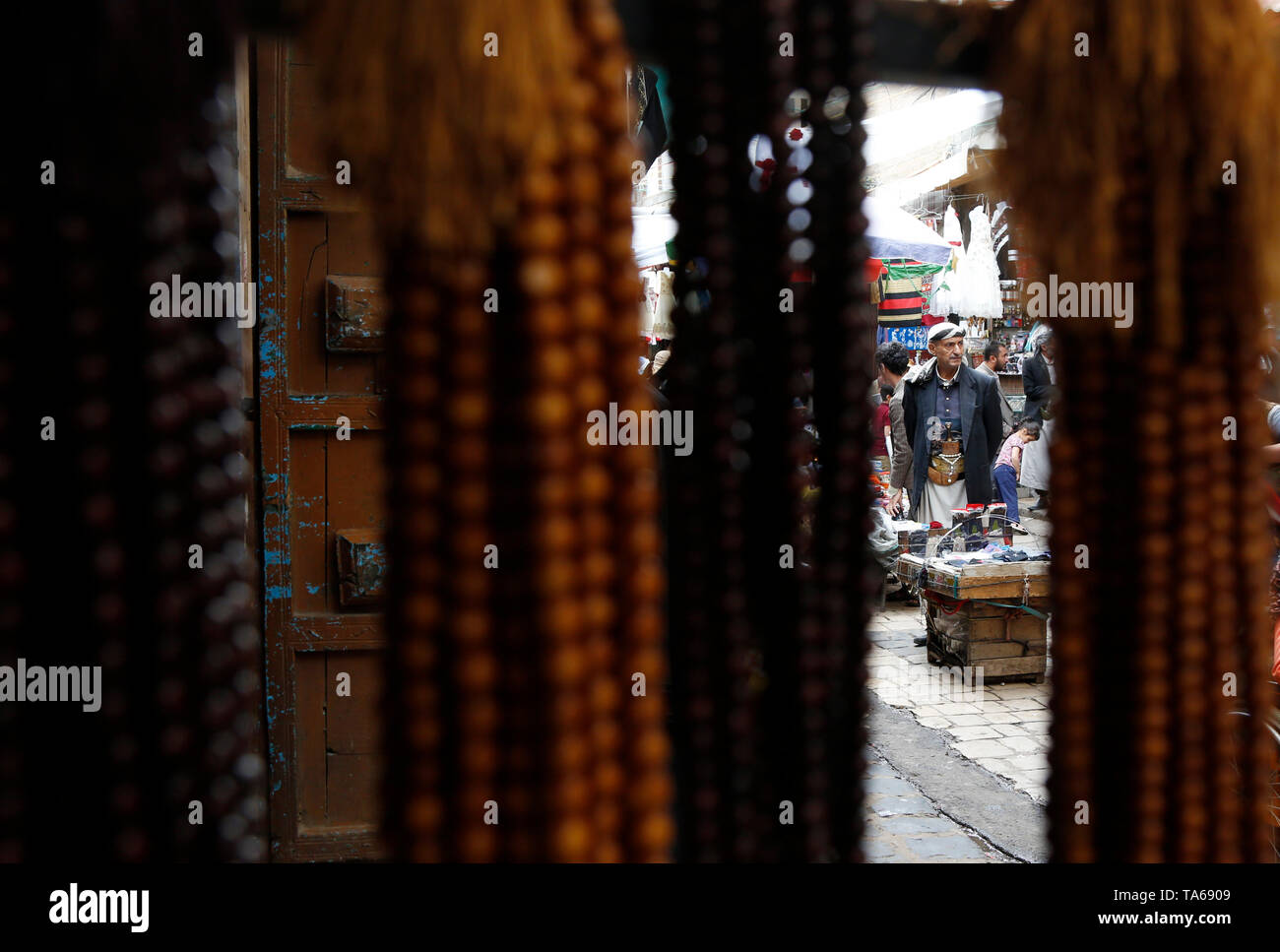 Sanaa, Yemen. 22nd May, 2019. A Yemeni man is seen through rosaries displayed for sale during the Muslim holy month of Ramadan in Sanaa, Yemen, on May 22, 2019. Rosary, or Tesbih, is a small string of prayer beads that is carried by many Yemeni men during the holy month of Ramadan. Credit: Mohammed Mohammed/Xinhua/Alamy Live News - Stock Image