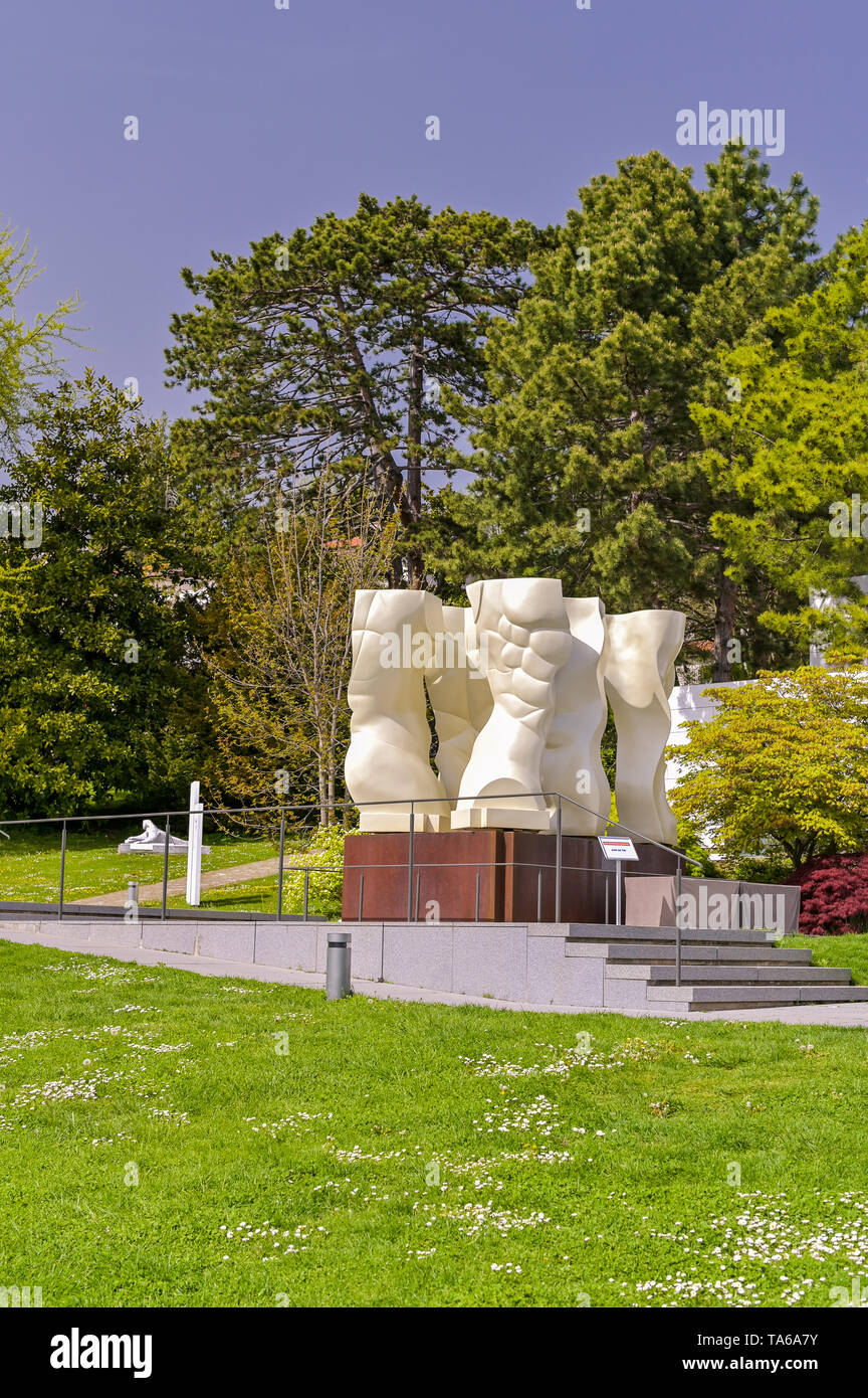 White large sculpture in the park of the Olympic Museum. Flowers and views of the mountains from the park - Stock Image