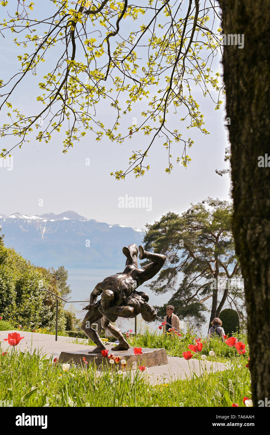 Sculpture in the park of the Olympic Museum. Flowers and views of the mountains from the park - Stock Image