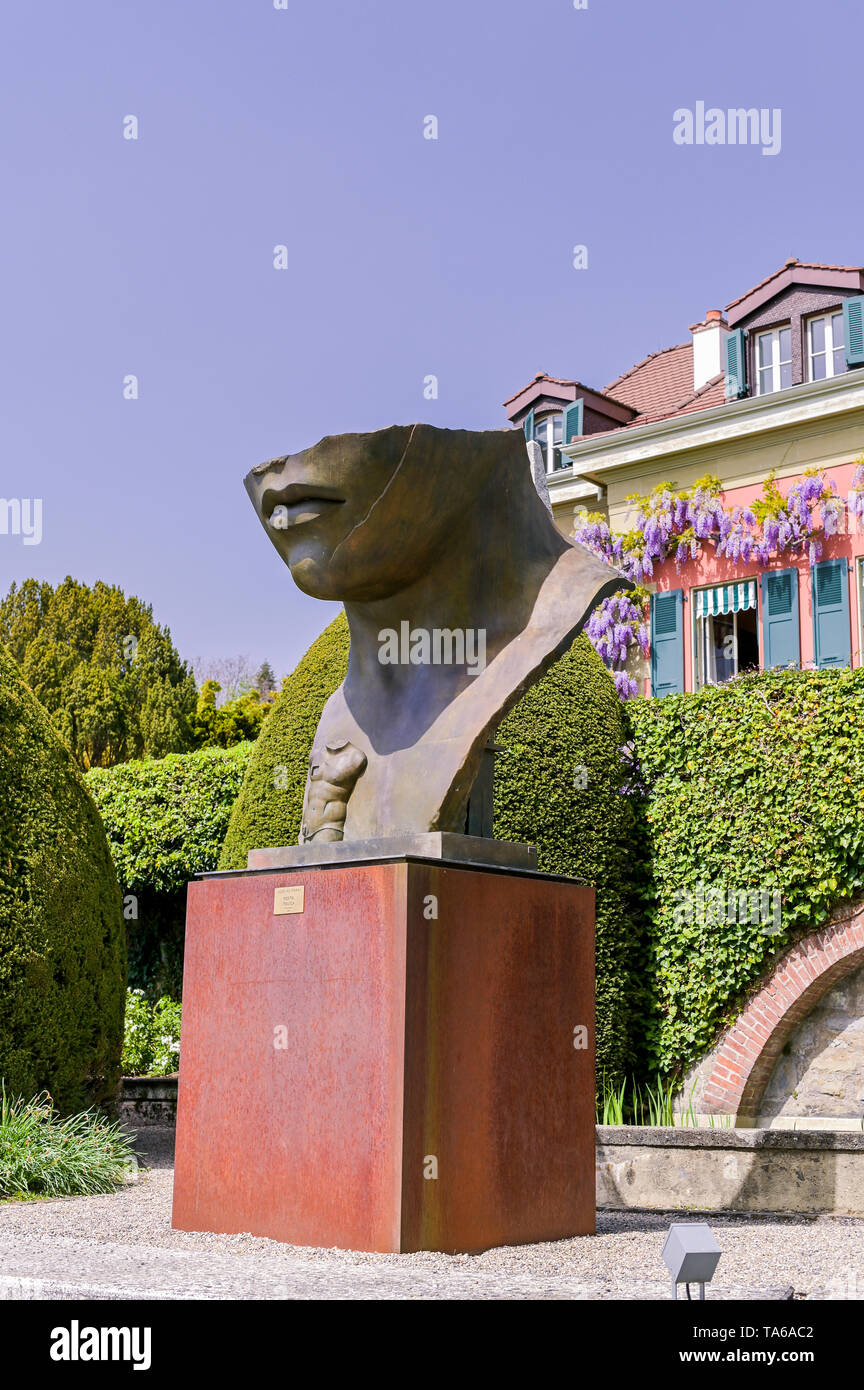 Sculpture of a large head in the park of the Olympic Museum of Switzerland. Spring grass and flowers in the park - Stock Image