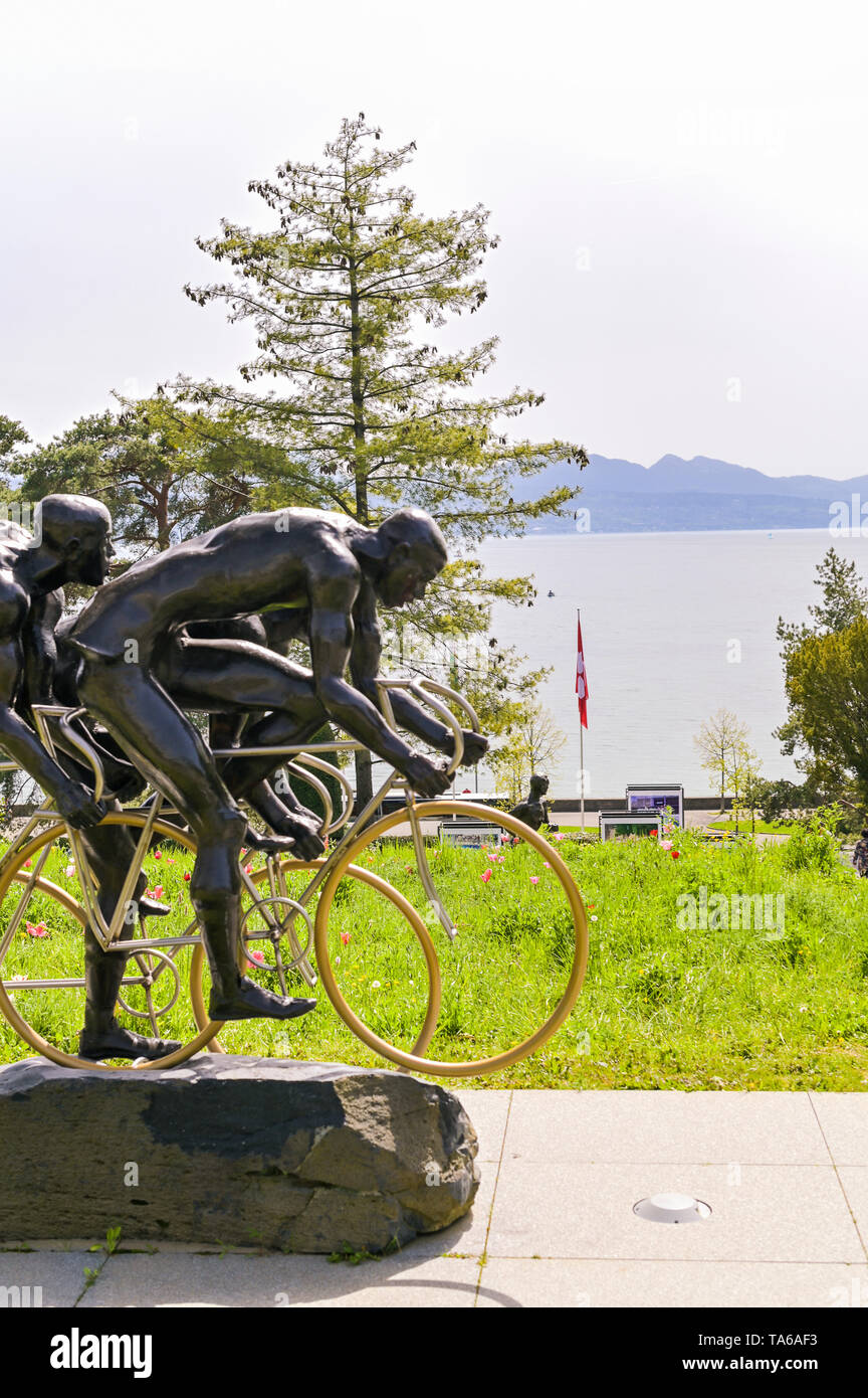 Sculpture of two cyclists in the park of the Olympic Museum in Switzerland. Spring grass and flowers in the park - Stock Image