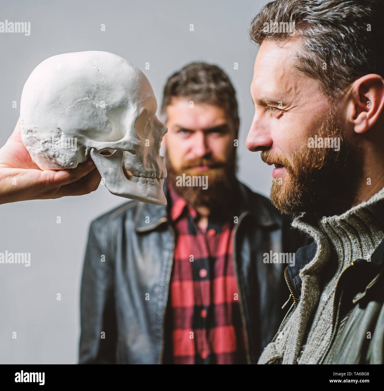 Focused on breaking fear. Psychology concept. Human fears and courage. Looking deep into eyes of your fear. Man brutal bearded hipster looking at skull symbol of death. Overcome your fears. Be brave. - Stock Image