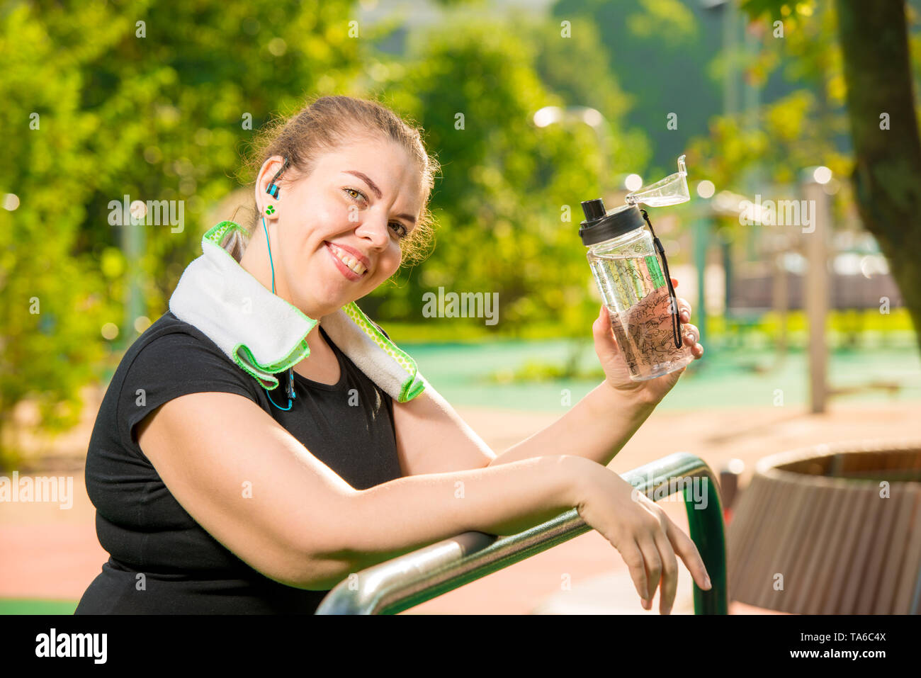 portrait of a happy oversized woman with a bottle of water smiling, portrait after a workout in the park - Stock Image