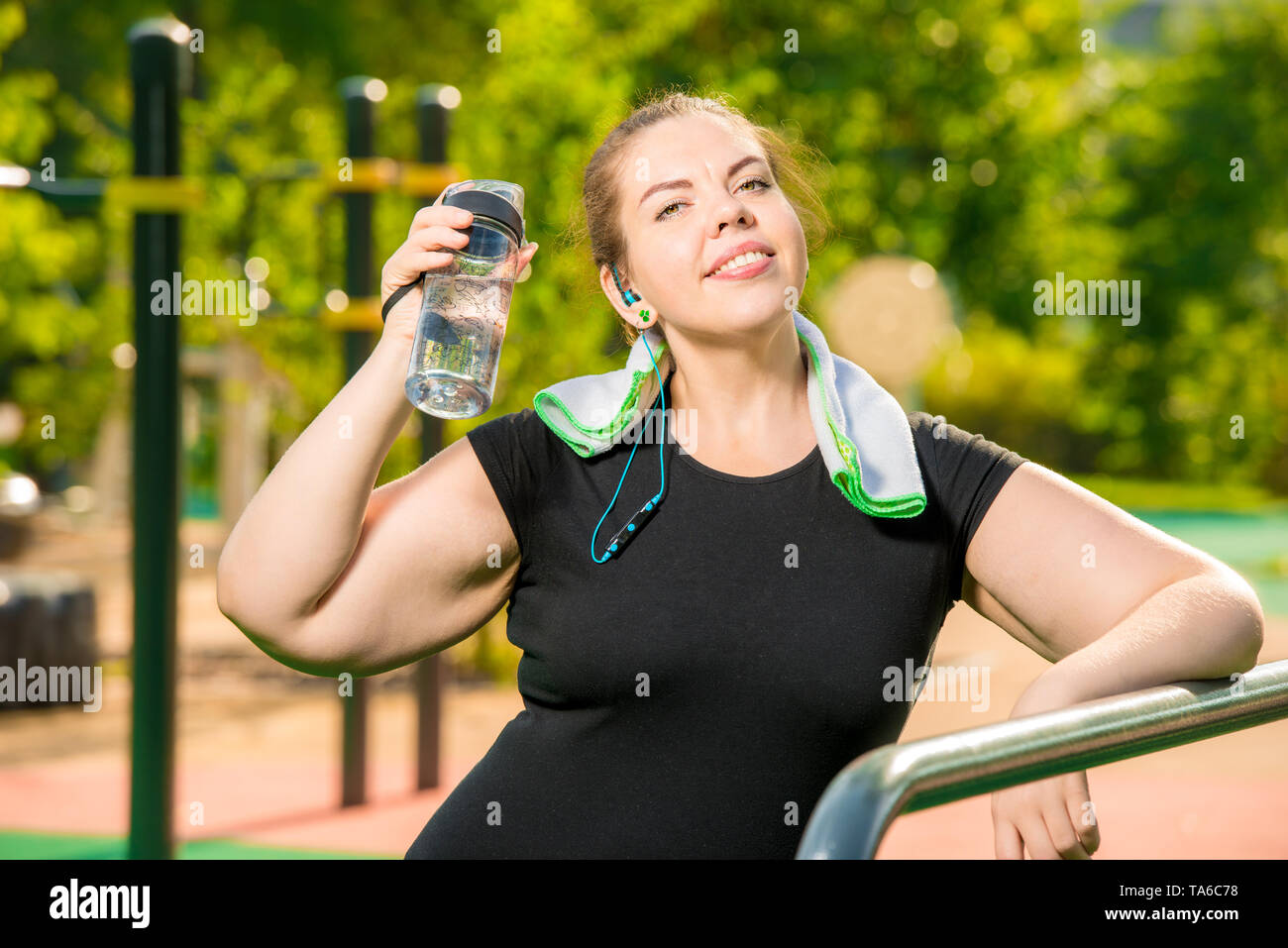 rest after training, portrait of a large woman with a bottle of water next to the simulator in the park - Stock Image
