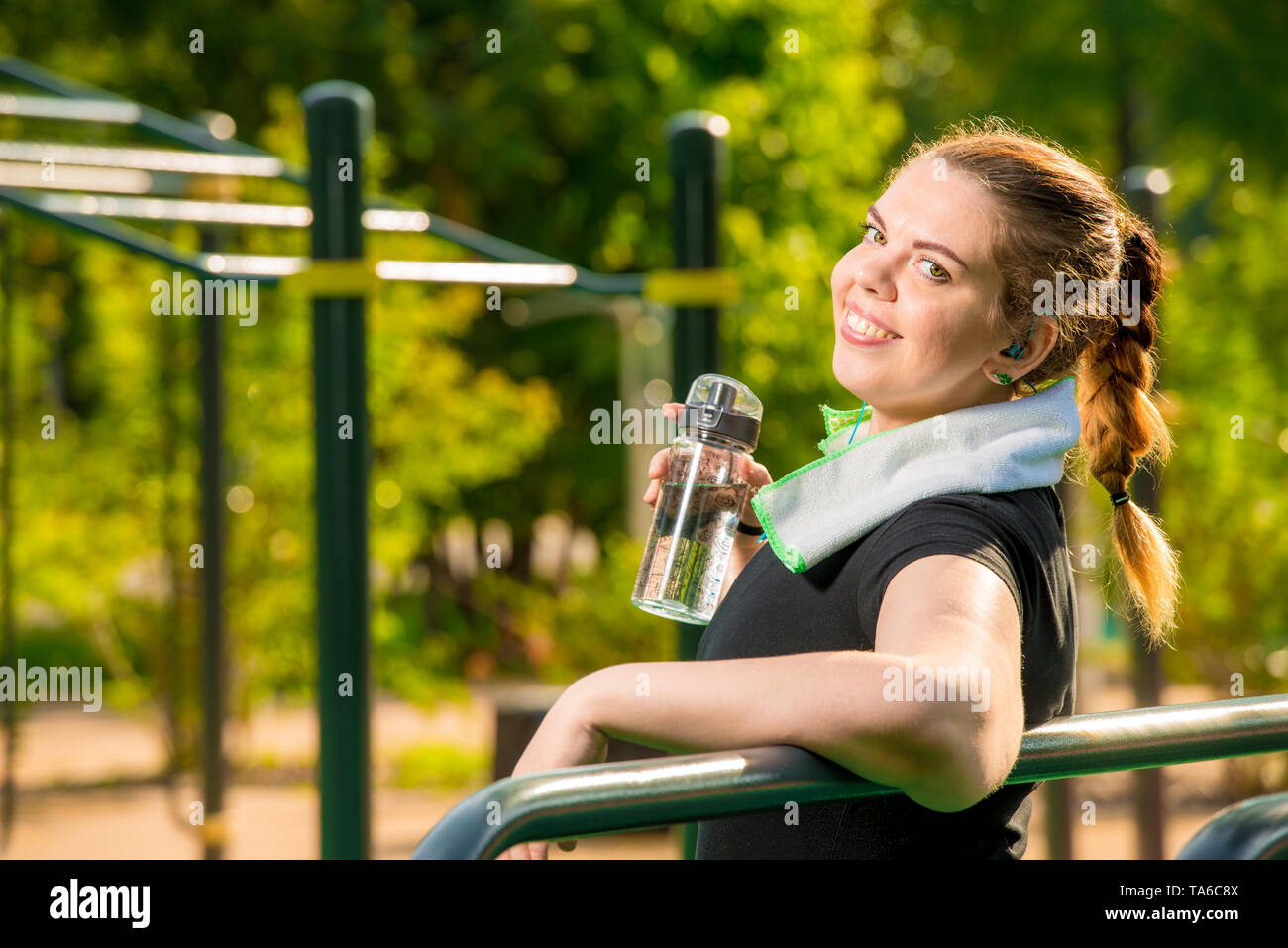 portrait of a happy fat woman with a bottle of water next to a simulator in the park - Stock Image