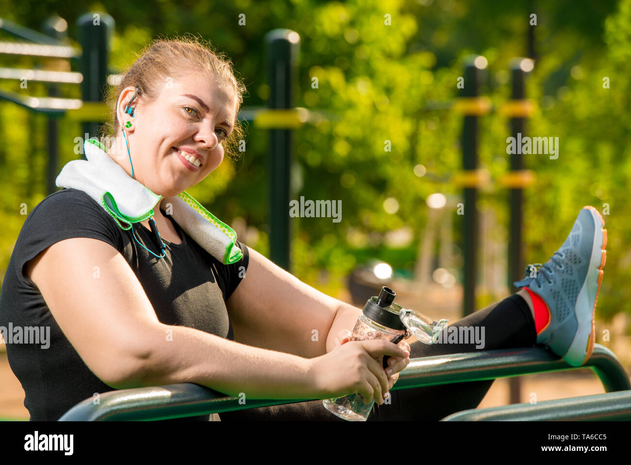 flexible plus size woman engaged with a port on the playground in a park on a summer morning - Stock Image