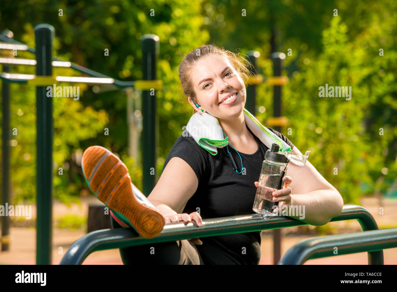 happy fat woman posing after workout in the park near the simulator - Stock Image