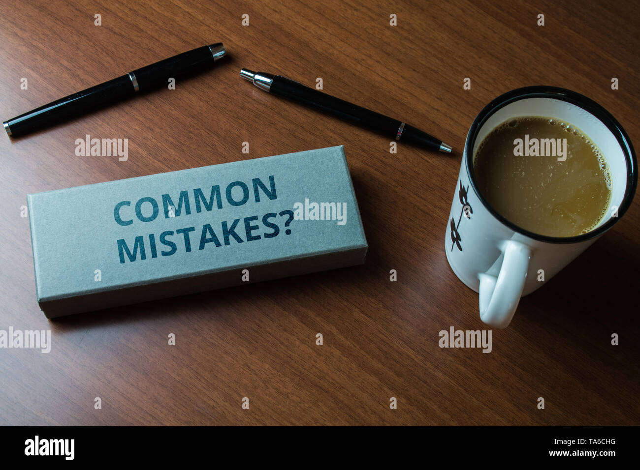 Word writing text Common Mistakes question. Business photo showcasing repeat act or judgement misguided or wrong Upper close view two ball point pens  - Stock Image