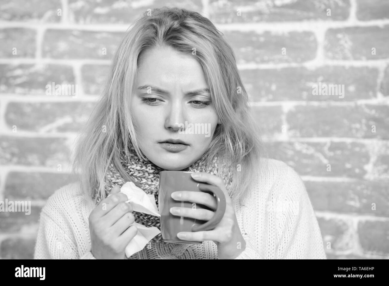 Drink more liquid get rid of cold. Drinking plenty fluid important for ensuring speedy recovery from cold. Girl hold tea mug and tissue. Runny nose and other symptoms of cold. Cold and flu remedies. - Stock Image