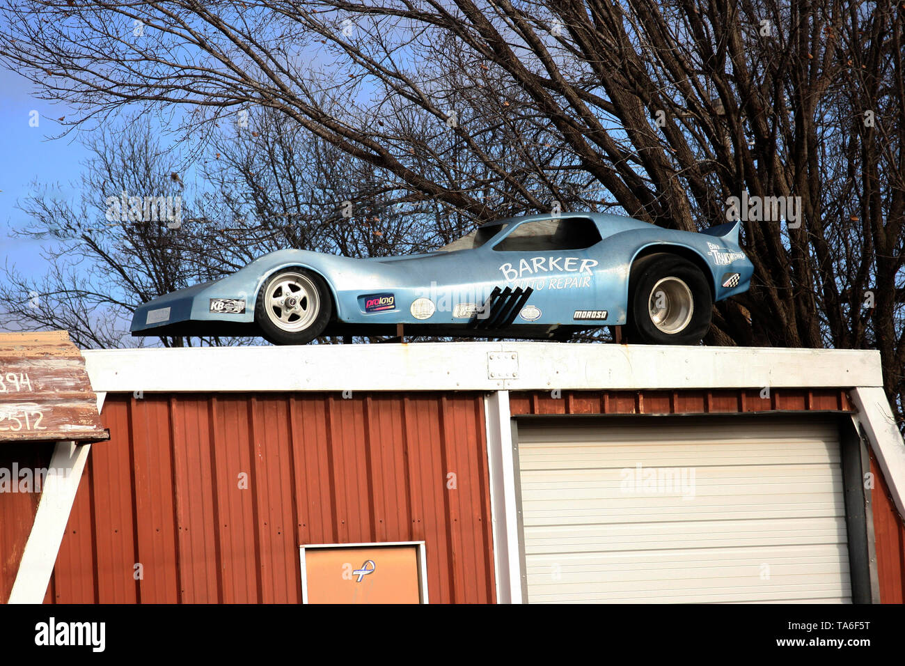 Sports car on top of a garage roof - Stock Image