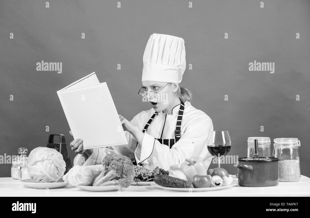 Woman chef cooking healthy food. Girl read book best culinary recipes. Culinary education concept. Female in hat and apron knows everything about culinary arts. Improve cooking skill. Culinary expert. - Stock Image