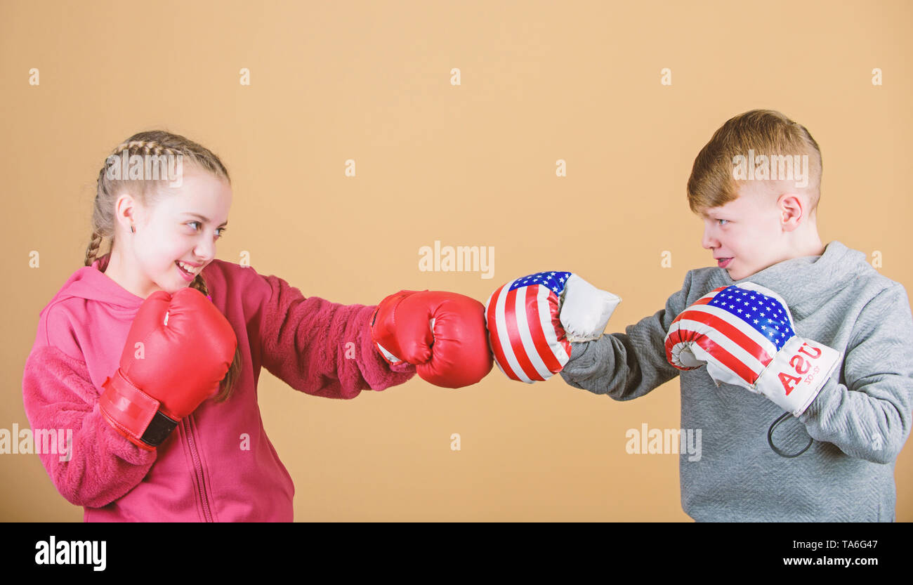 Girl and boy boxing competitors. Battle for attention. Child sporty athlete practicing boxing skills. Boxing sport. Children wear boxing gloves while fighting beige background. Attack and defend. - Stock Image